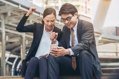 Homme heureux et femme d'affaires regardant le téléphone Photos stock