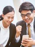 Homme heureux et femme d'affaires regardant le téléphone Image libre de droits