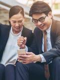 Homme heureux et femme d'affaires regardant le téléphone Photos libres de droits