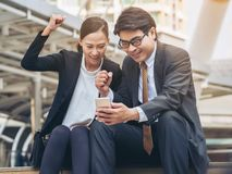 Homme heureux et femme d'affaires regardant le téléphone Image stock