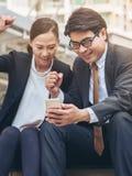 Homme heureux et femme d'affaires regardant le téléphone Photographie stock libre de droits
