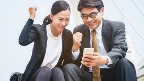 Homme heureux et femme d'affaires regardant le téléphone Photo stock