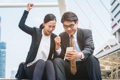 Homme heureux et femme d'affaires regardant le téléphone Photographie stock