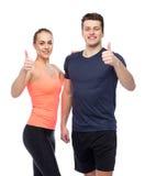 Homme heureux et femme folâtres montrant des pouces  Photographie stock