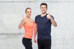 Homme heureux et femme folâtres montrant des pouces  Photo libre de droits