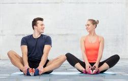 Homme heureux et femme folâtres s'asseyant sur des tapis Photos libres de droits