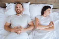 Homme heureux et femme folle se situant dans le lit ensemble Photographie stock