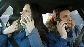 Homme heureux et femme parlant leurs téléphones portables et s'asseyant dans la voiture Front View clips vidéos