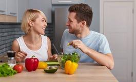 Homme heureux et femme préparant la salade végétale image libre de droits