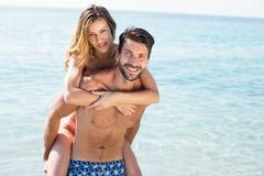 Homme heureux ferroutant l'amie sur le rivage à la plage Images libres de droits
