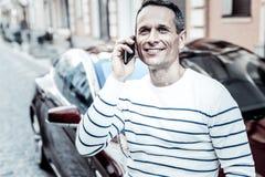 Homme heureux gai ayant une conversation téléphonique Photographie stock