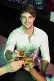 Homme heureux grillant son verre de bière Photographie stock libre de droits