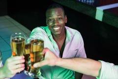 Homme heureux grillant son verre de bière Photos stock