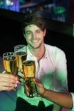 Homme heureux grillant son verre de bière Image stock