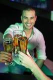 Homme heureux grillant son verre de bière Image libre de droits