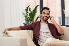 Homme heureux invitant le smartphone à la maison Photographie stock libre de droits