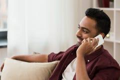 Homme heureux invitant le smartphone à la maison Photographie stock