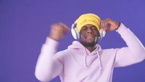 Homme heureux joyeux de hippie dans le hoodie blanc avec le capot sur la musique de écoute avec des écouteurs banque de vidéos