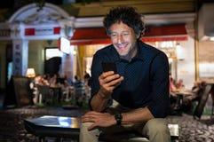 Homme heureux mûr à l'aide du téléphone la nuit photographie stock libre de droits