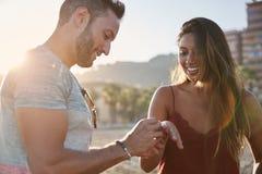Homme heureux mettant la bague de fiançailles sur le doigt d'amie Photo libre de droits
