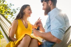 Homme heureux mettant la bague de fiançailles sur le doigt de l'amie dessus Photo libre de droits