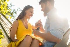 Homme heureux mettant la bague de fiançailles sur le doigt de l'amie dessus Image libre de droits