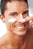 Homme heureux mettant la lotion de bronzage sur le visage Image libre de droits