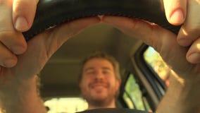 Homme heureux mettant ses mains sur le volant en cuir de la voiture, couleurs chaudes vidéo 4K banque de vidéos