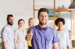 Homme heureux montrant des pouces au-dessus d'équipe dans le bureau Photo stock