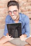 Homme heureux montrant l'écran vide de sa protection de comprimé Image stock