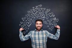 Homme heureux montrant le biceps et la position sur le fond de tableau noir Image stock