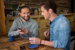 Homme heureux montrant le téléphone intelligent à l'ami dans le café Photo libre de droits