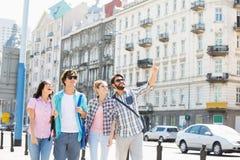 Homme heureux montrant quelque chose aux amis sur la rue de ville Photographie stock