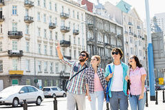 Homme heureux montrant quelque chose aux amis sur la rue de ville Image stock