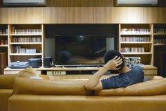 Homme heureux observant un film dans le salon la nuit photos libres de droits