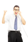 Homme heureux parlant à un téléphone et faisant des gestes le bonheur Photos stock