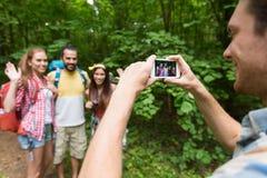 Homme heureux photographiant des amis par le smartphone Photographie stock libre de droits