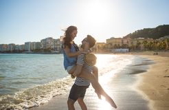 Homme heureux portant son amie au bord de la mer Image stock