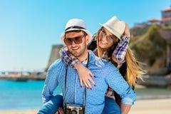Homme heureux portant son amie sur un tour de ferroutage souriant et regardant très heureuse appréciant leurs vacances Images libres de droits
