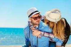 Homme heureux portant son amie sur un tour de ferroutage souriant et regardant très heureuse appréciant leurs vacances Photos stock