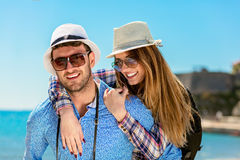 Homme heureux portant son amie sur un tour de ferroutage souriant et regardant très heureuse appréciant leurs vacances Photographie stock