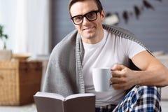 Homme heureux positif se reposant à la maison Image stock