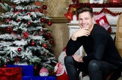 Homme heureux près de la cheminée Noël et an neuf Photographie stock