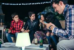 Homme heureux regardant le smartphone en partie avec des amis Photo stock