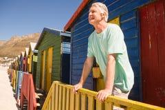 Homme heureux regardant parti tout en se tenant la hutte de plage Photographie stock