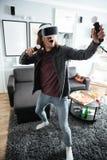 Homme heureux reposant à la maison à l'intérieur des jeux de jeu Image libre de droits