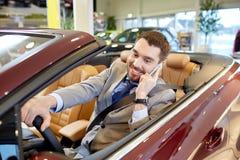 Homme heureux s'asseyant dans la voiture au salon de l'Auto ou au salon Photo stock