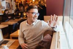 Homme heureux s'asseyant en café tout en saluant des amis Photo libre de droits