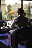 Homme heureux s'asseyant et travaillant sur l'ordinateur portatif Photographie stock