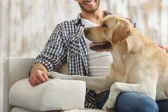 Homme heureux s'asseyant sur un divan avec son ami d'animal familier Photo libre de droits